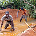 Tetra Tech's team supports artisanal miners as they dredge water in a pit.