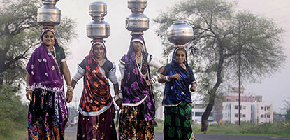 Women in India carry water back to their rural village.