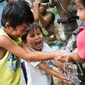 A group of Pilipino children laughing and playing with water from a water pump.