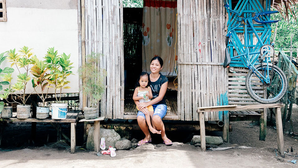 A Pilipino woman sitting on her stoop with her child on her lap smiling.