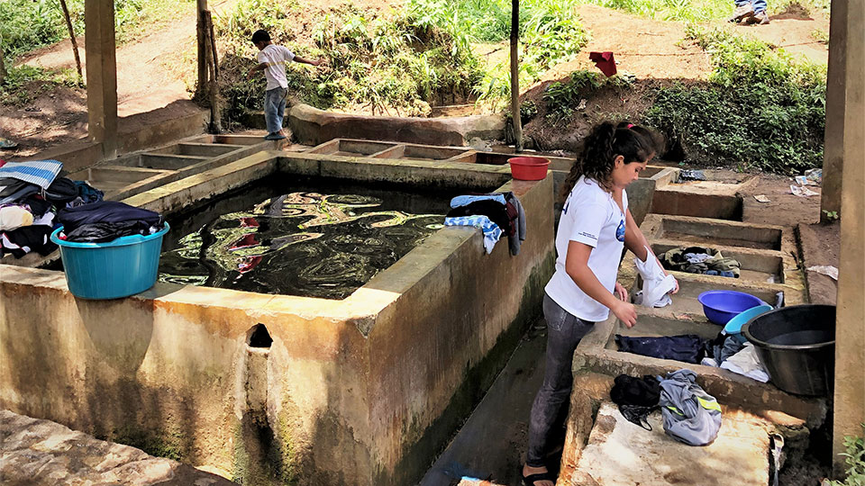 A woman in La Reforma is uses the community water to wash her family's clothes.
