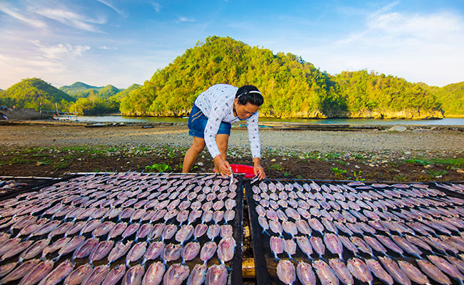 A local fisherwoman dries fish to prepare them for eating.
