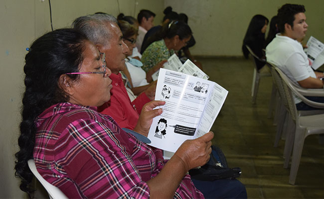 An older adult reviews a Participant Workbook during a workshop about the right to access public information.