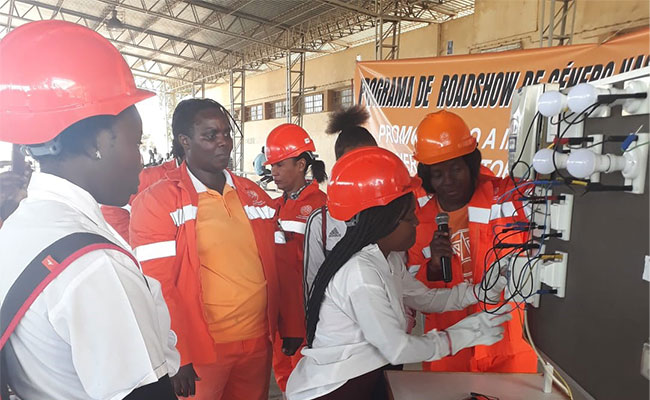 A young woman from Mozambique engages with an interactive electricity display at the Engendering Utilities road show.