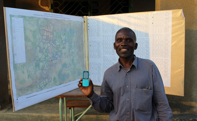 Zambian community volunteer displays the new database tool on his mobile phone in front of his community's mapped land