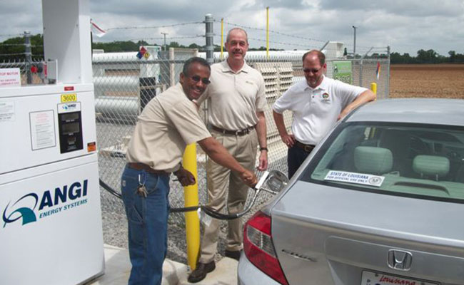 Tetra Tech team members fill car with green fuel.