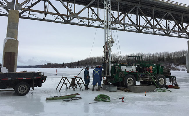 Tetra Tech staff monitor on-ice drilling operations on a river.