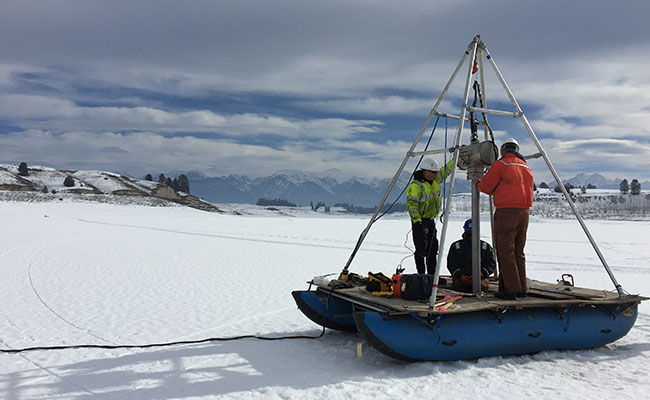 Tetra Tech staff monitor through-ice vibracore sediment sampling on a water reservoir.