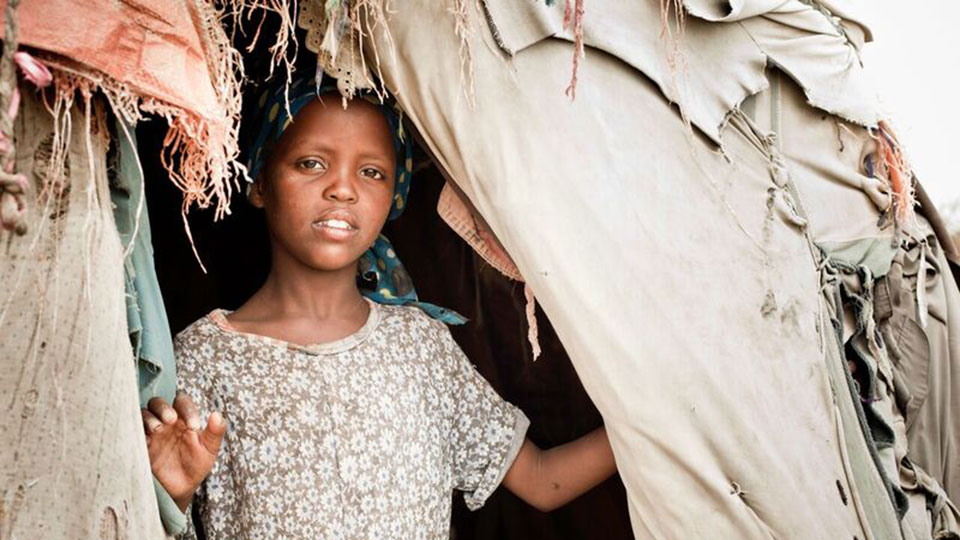 Young Somali girl looks out from her hut at an IDP camp.