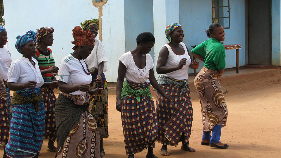 Members of community dance troop and Chipata District Land facilitator, Misozi Banda celebrate land certificates.
