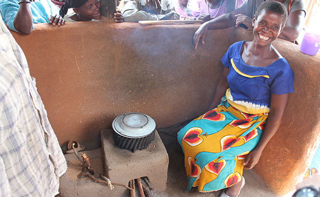 Woman in her cooking area sits next to her energy efficient cookstove.