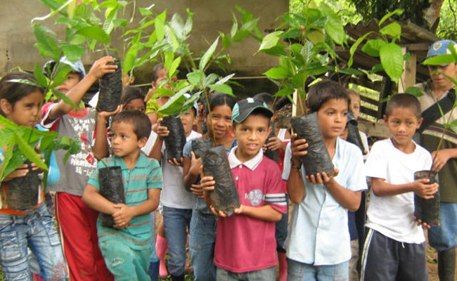 Local children prepare to plant new tree seedlings as part of a youth outreach program