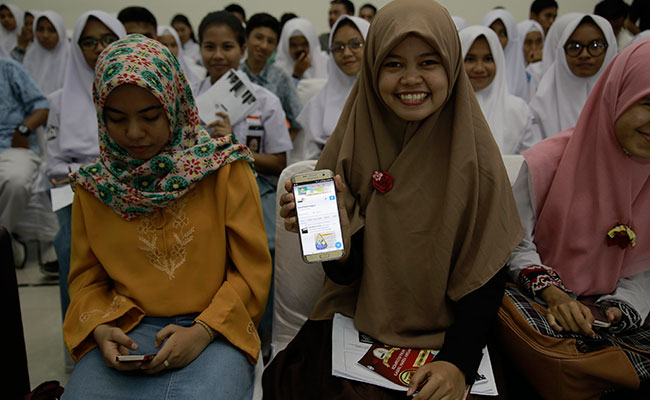 A student visits the official film festival Twitter page on her mobile phone