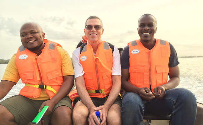 Lamine (pictured right) travels by boat with his team members to a WA-BiCC project site in Ghana