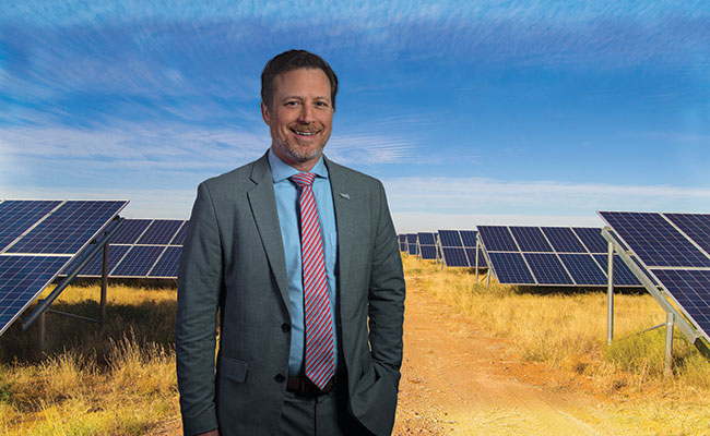 Andrew M. Herscowitz stands in front of solar panels in a field in Africa