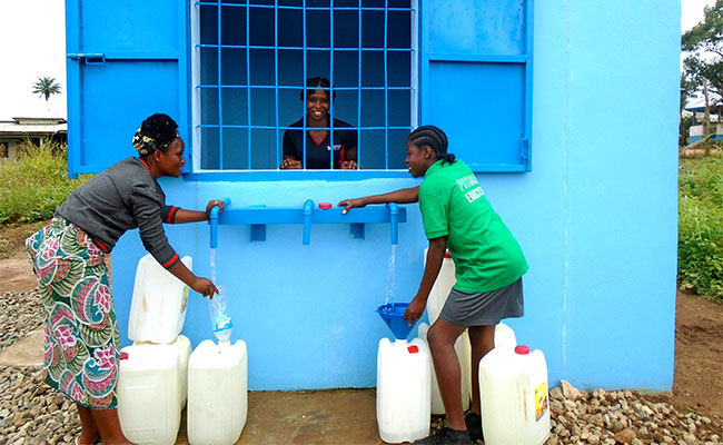 Liberians purchase safe drinking water at a public kiosk