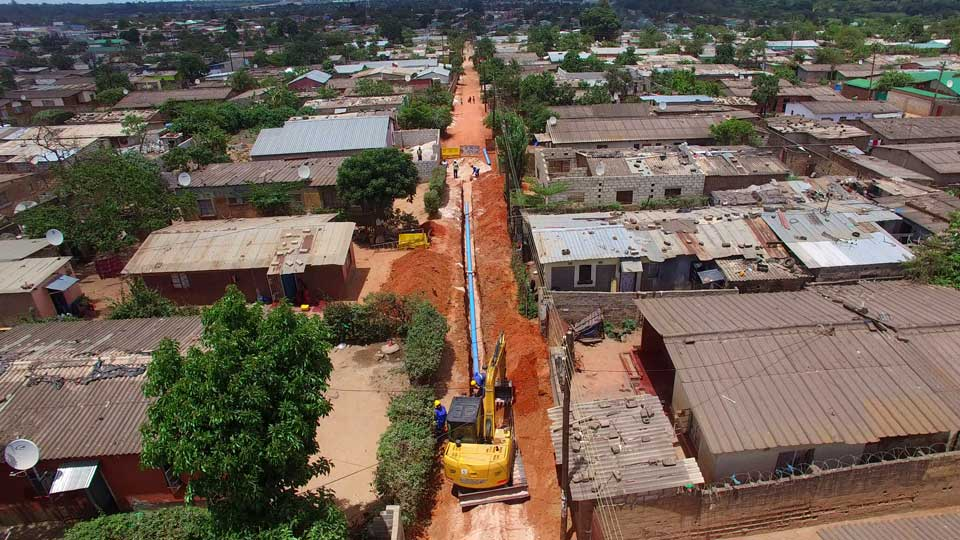 Construction equipment and workers shown from overhead working on the Lusaka Water Supply, Sanitation, and Drainage Proj