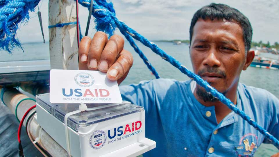 A fisherman holds up a USAID label that is part of the electronic Catch Documentation and Traceability.