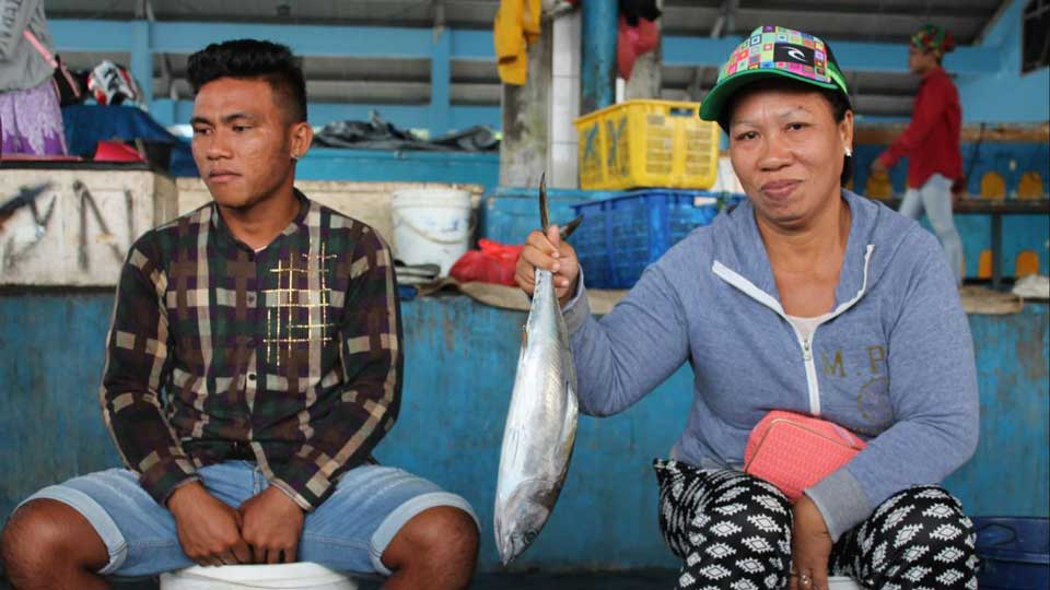 Two fisherfolk pose with a catch and equipment that is part of the electronic USAID Oceans electronic Catch Documentatio