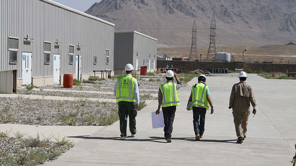 Four Tetra Tech staff are walking together on site at an electrical engineering project.