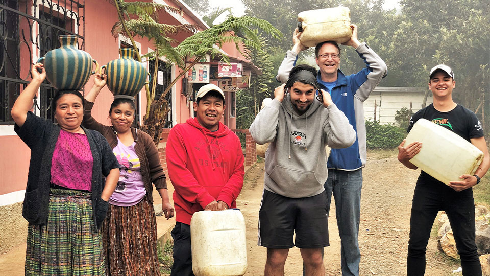 A group of people helping Mayan villagers in Guatemala carry water jugs to their homes.