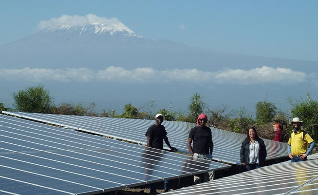 PATRP BTG Transaction Advisor, Carolina Barreto, at a mini-grid installation in Kenya, with Mt. Kilimanjaro in the back.