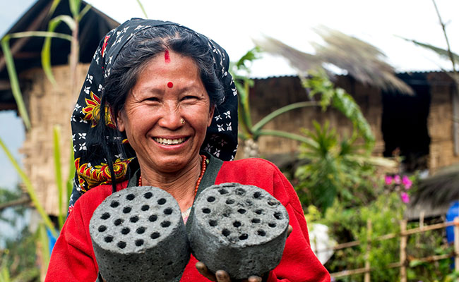 A woman shows her bio-briquettes after a briquette production training in India.