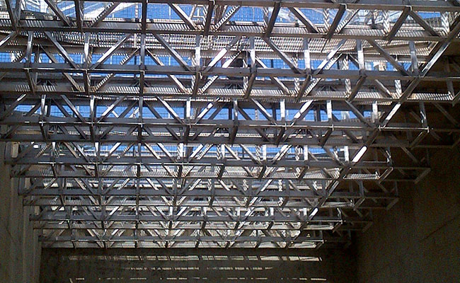 A view from the floor of the bioreactor looking up at the baskets to contain the plants and greenhouse glass roof above
