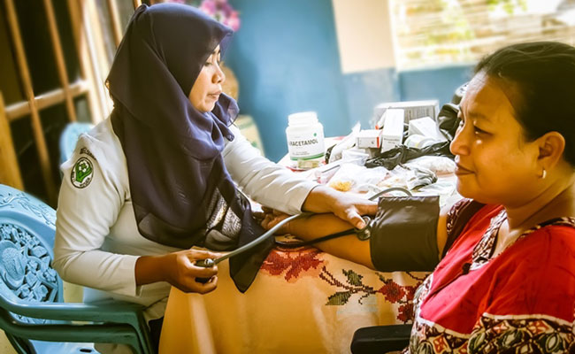 A nurse checks a patient's blood pressure at a government-mandated Puskesmas health clinic.