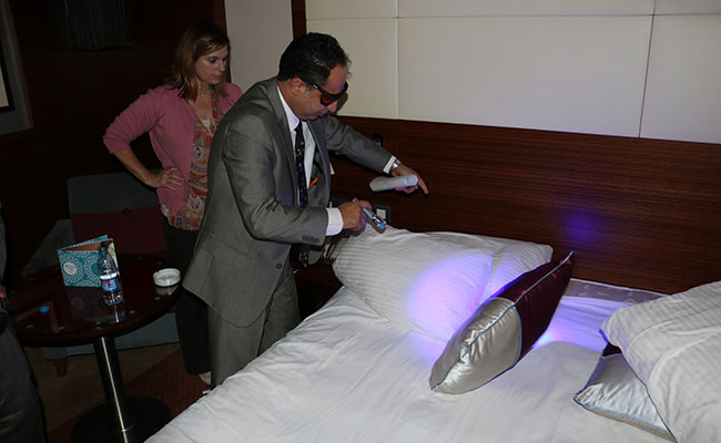 Jordanian prosecutor inspecting a mock crime scene with ultra-violet forensic technology for evidence as part of a train