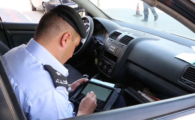 Police officer uses new tablet technology to check vehicle registration during a traffic stop
