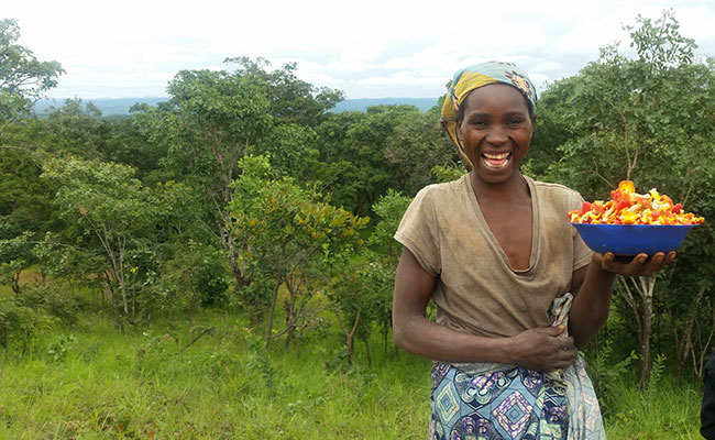 A woman outside Perekezi Forest Reserve, a PERFORM project site, proudly holds her non-timber forest product, wild mushr