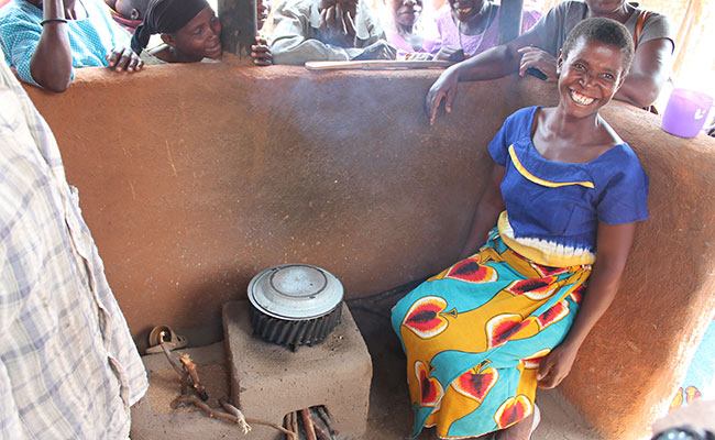 A woman smiles proudly after showing her improved cookstove, which is estimated to be 28 percent more fuel efficient tha