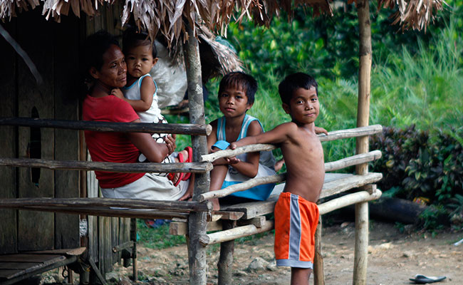 Children stand in front of their family's hut in the Philippines
