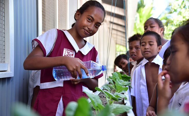 School children tending their school's community garden, developed as part of the school refurbishment delivered by KEIP