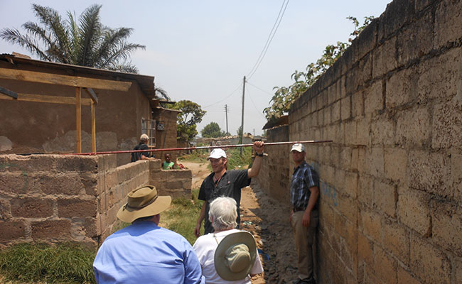 A man measures the width of a proposed construction corridor to assess impacts to existing structures in a Zambian villa