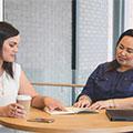Duas empresárias Maoris sentadas a uma mesa discutindo sobre trabalho.
