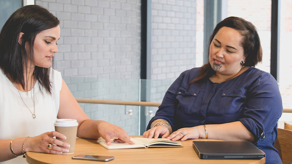 Two Maori businesswomen sitting at a table and discussing work.