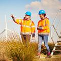 Dois engenheiros de parques eólicos vestindo colete refletivo enquanto estão em atividade de campo próximos a equipament