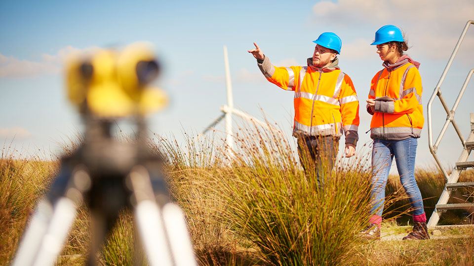 Two wind farm engineers wearing high visibility gear while in the field near survey equipment and wind turbines.