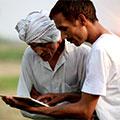 Dois colaboradores internacionais usando um tablet no campo para reportes de saúde e segurança.