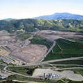 Aerial view of landfill surrounded by green hills.
