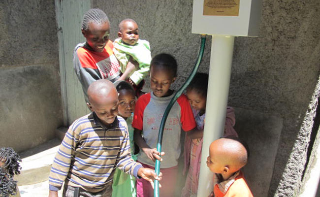 Children in Kenya access water at a water point established by the SUWASA program