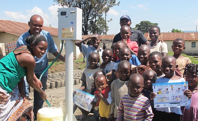 Children getting clean drinking water from a faucet and pump