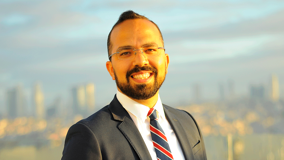 Dr. Reza Malehmir pictured outside wearing a suit and tie