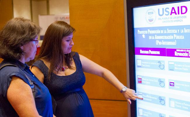 Pro-Integridad's Flor Torres utilizes the touchscreen to learn more about the project's achievements