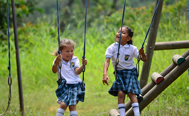 Two young girls enjoy a new swingset at their school in Tolima